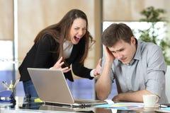 Affärskvinna som retar en allmäntjänstgörande läkare på kontoret royaltyfri bild