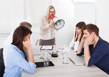 Affärskvinna som ropar till och med megafonen på kollegor royaltyfri foto