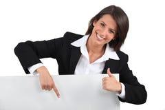 Affärskvinna som rymmer det blanka meddelandebrädet Arkivfoto