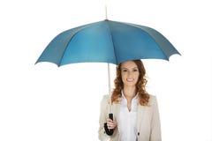 Affärskvinna som rymmer ett paraply arkivfoto