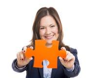 Affärskvinna som rymmer ett pusselstycke arkivbild