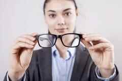 Affärskvinna som rymmer glasögon i händer på grå bakgrund royaltyfri bild