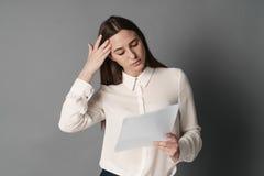 Affärskvinna som rymmer hans head läsningdokument på grå bakgrund Stående av affärskvinnan Royaltyfri Foto