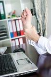 Affärskvinna som rymmer hennes smärtsamma handled Arkivbild