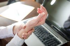 Affärskvinna som rymmer hennes smärtsamma handled Arkivfoton