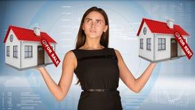 Affärskvinna som rymmer hus två med etiketter till salu Royaltyfri Foto
