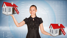 Affärskvinna som rymmer hus två med etiketter till salu Fotografering för Bildbyråer