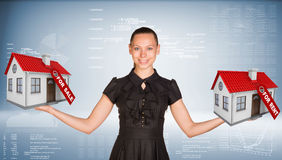Affärskvinna som rymmer hus två med etiketter till salu Arkivbild