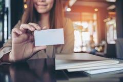 Affärskvinna som rymmer och visar ett tomt affärskort med anteckningsböcker på tabellen arkivbild