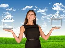 Affärskvinna som rymmer två hus som, om chosing Arkivbild