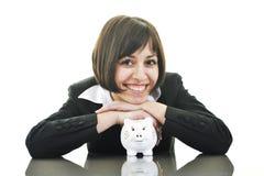 Affärskvinna som sätter myntpengar i den piggy gruppen Royaltyfria Bilder