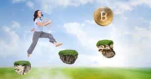 Affärskvinna som samlar bitcoins som hoppar på modiga plattformar i himmel royaltyfria foton