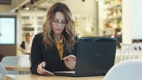 Affärskvinna som samtidigt arbetar på bärbara datorn och smartphonen en kvinna i en affärsdräkt som arbetar i ett informellt lager videofilmer