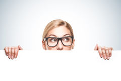 Affärskvinna som ser över överkant av det vita tecknet Arkivbilder