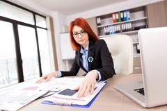 Affärskvinna som ser diagram och diagram i hennes kontor Arkivbild