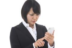 Affärskvinna som ser en smartphone Arkivbilder