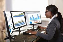 Affärskvinna som ser grafer på datoren arkivbild