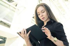 Affärskvinna som ser in i anteckningsboken på bakgrund av byggnad Royaltyfri Foto