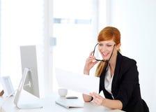 Affärskvinna som ser in i legitimationshandlingar Arkivbild