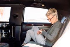 Affärskvinna som ser klockan i limousine Royaltyfri Bild