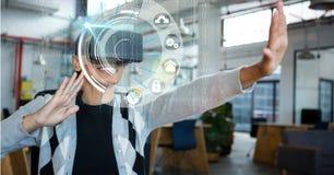 Affärskvinna som ser symboler till och med VR-exponeringsglas Royaltyfri Bild