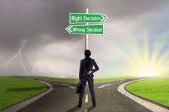 Affärskvinna som ser tecknet av rätten vs fel beslut royaltyfri bild