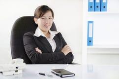 Affärskvinna som sitter med korsade armar Royaltyfri Bild
