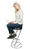 Affärskvinna som sitter på en hög stol och arbeten Arkivfoton