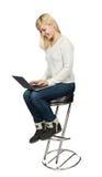 Affärskvinna som sitter på en hög stol och arbeten Royaltyfri Bild