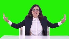 Affärskvinna som sitter på en tabell på arbete och att skrika Svänger hans armar stock video