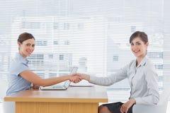 Affärskvinna som skakar händer med intervjuobjektet och båda som ler på Arkivbild