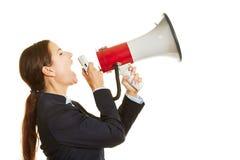 Affärskvinna som skriker in i megafonen arkivfoton