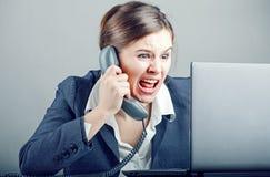Affärskvinna som skriker in i telefonen Royaltyfri Bild