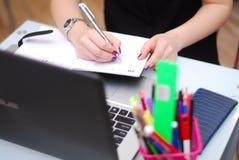 Affärskvinna som skriver en anmärkning i en anteckningsbok Arkivbilder
