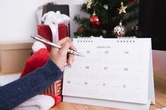 Affärskvinna som skriver kalenderstadsplaneraren i julferie arkivfoton