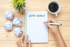 Affärskvinna som skriver 2019 mål med anteckningsboken, smulat papper och koppen för svart kaffe på tabellen Start för nytt år so arkivfoto