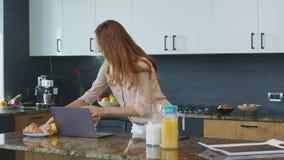 Affärskvinna som skyndsamt förbereder frukosten Upptagen moder som kör för att arbeta arkivfilmer