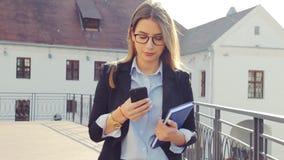 Affärskvinna som smsar på smartphonen i staden stock video