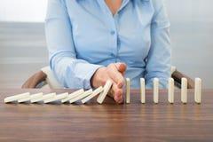 Affärskvinna som stoppar effekten av dominobricka Royaltyfri Fotografi
