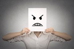 Affärskvinna som täcker hennes framsida med den ilskna maskeringen Royaltyfri Fotografi