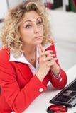Affärskvinna som tänker på hennes skrivbord arkivfoton
