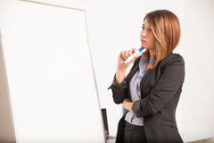 Affärskvinna som tänker vad för att skriva på ett bräde Fotografering för Bildbyråer