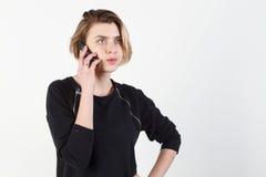 Affärskvinna som talar på den mycket emotionella telefonen Hon ler, retar upp, agression som missförstås, övergrepp På en vit Royaltyfria Foton