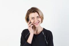 Affärskvinna som talar på den mycket emotionella telefonen Hon ler, retar upp, agression som missförstås, övergrepp På en vit Arkivfoto