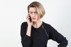 Affärskvinna som talar på den mycket emotionella telefonen Hon ler, retar upp, agression som missförstås, övergrepp På en vit Royaltyfri Foto