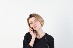 Affärskvinna som talar på den mycket emotionella telefonen Hon ler, retar upp, agression som missförstås, övergrepp På en vit Arkivbilder