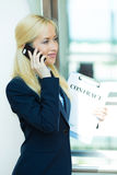 Affärskvinna som talar på en telefon som rymmer avtalsdokument Royaltyfria Foton