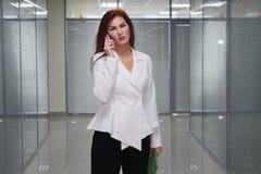 Affärskvinna som talar på mobiltelefonen i korridor av kontoret royaltyfria bilder