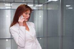 Affärskvinna som talar på mobiltelefonen i korridor av kontoret royaltyfri foto