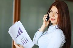 Affärskvinna som talar på mobiltelefonen, ler och ser kameran grunt djupfält royaltyfri bild